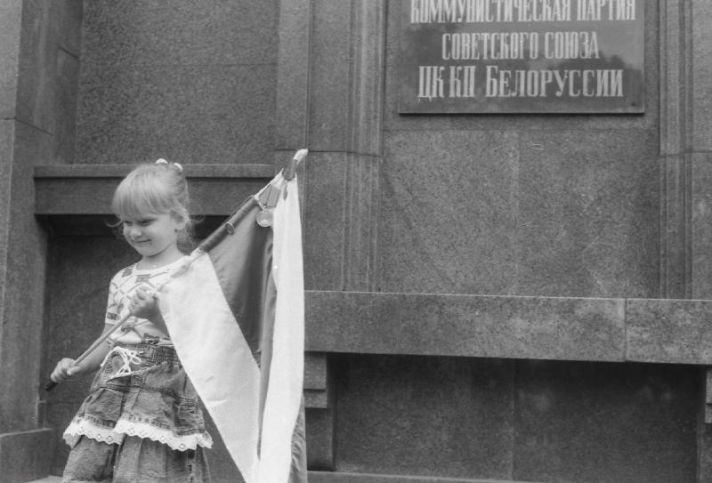 Дзяўчынка з бел-чырвона-белым сцягам каля будынка ЦК КПБ